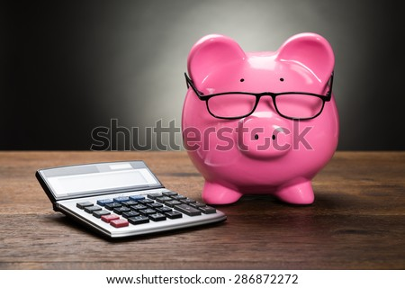 Pink Piggybank With Calculator On Wooden Table - stock photo