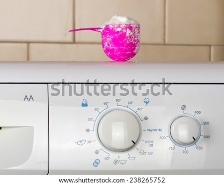 Pink plastic cup with washing powder on the top of washing machine in bathroom - stock photo