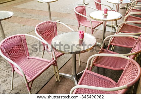 Pink plastic wicker chairs and round silver tables with pink cups containing sugar outside a bistro.  - stock photo