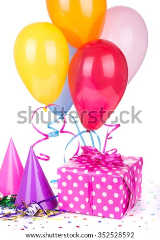 Pink polka dot birthday present with party hats and balloons on a white background - stock photo