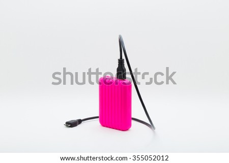 Pink portable usb power bank with usb 2.0 charging cable for mobile phone rotate 135 degrees isolated on white background - stock photo