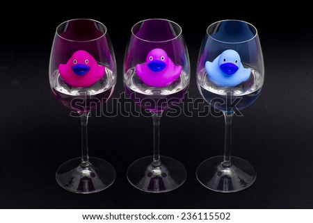 Pink, purple and blue rubber ducks in wineglasses, dark background - stock photo