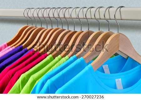 Pink, purple, crimson, bright green and turquoise women's T-shirts hanging on wooden hangers on gray background - stock photo