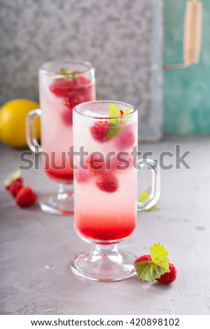 Pink refreshing cold raspberry lemonade in tall glasses