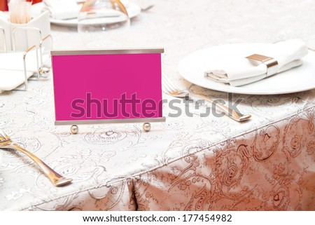 Pink Reserved sign on a table in restaurant - stock photo