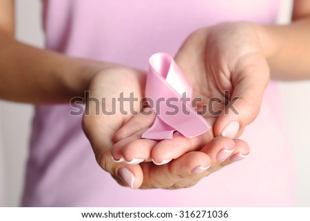 Pink ribbon in woman's hands close up - stock photo