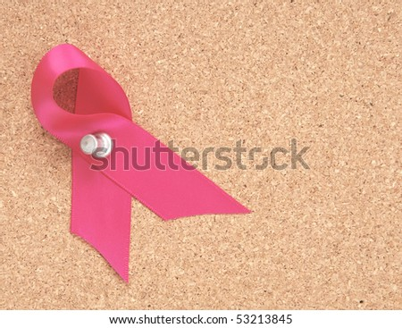 pink ribbon pinned to a corkboard to remember breast cancer awareness