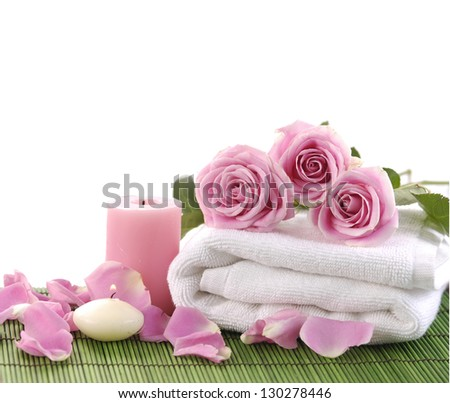 pink rose and towel with candle on green mat - stock photo