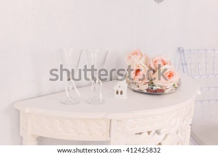 Pink rose on wooden table background with  glasses. Romantic floral theme