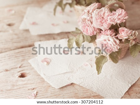 Pink rose on wooden table background with retro glasses and white hand made paper as a copy space, Romantic floral theme - stock photo