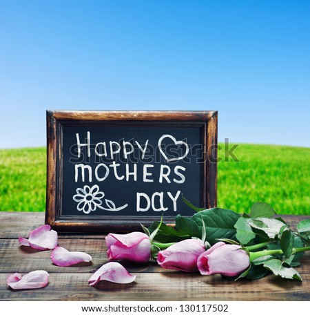 pink roses and congratulations on Mother's Day on the background field - stock photo