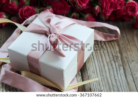 Pink roses and gift box over wooden table, holiday background, selective focus