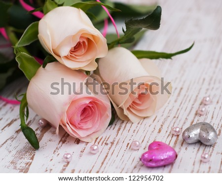 Pink Roses and hearts on a wooden background