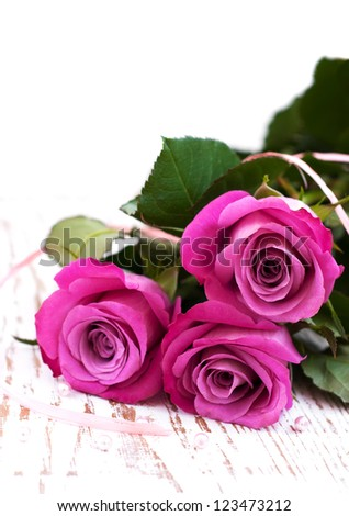 Pink Roses and pearls on a wooden background - stock photo