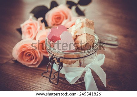 Pink roses and two valentine's paper hearts in retro jar on wooden background. Toned picture - stock photo