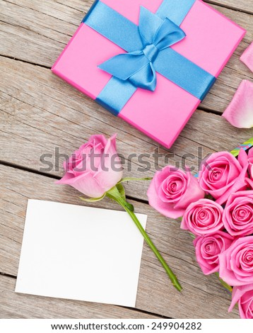 Pink roses and valentines day greeting card or photo frame and gift box over wooden table. Top view with copy space - stock photo