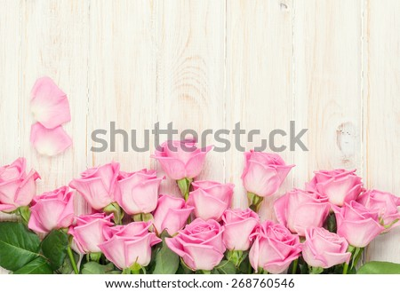 Pink roses bouquet over wooden table. Top view with copy space - stock photo
