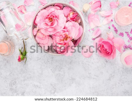Pink roses cosmetics set with cream,bottle,candles, petals and sea salt, spa background with space for text, top view - stock photo