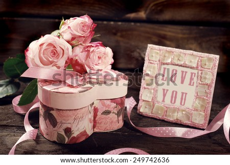 pink roses , heart shaped gift box and frame on wooden background in vintage style  - stock photo