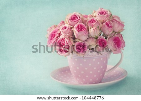 Pink roses in a cup on blue background - stock photo