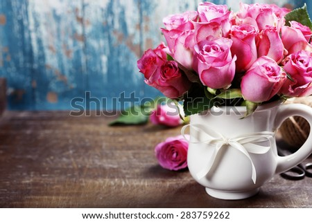 Pink roses in a pot on blue background  - stock photo