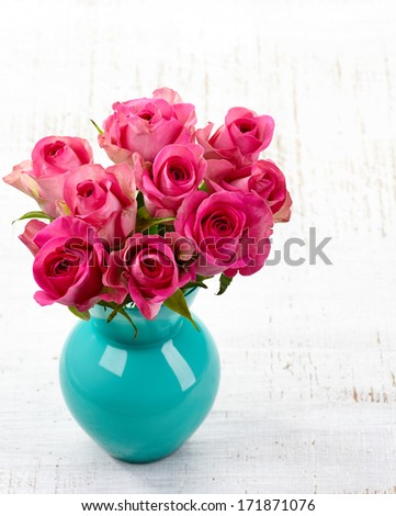 Pink roses in a vase on white wooden background - stock photo