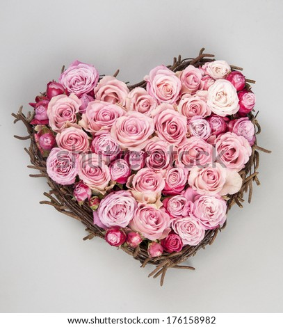 Pink roses in heart shape in a wooden weaving on gray background ...