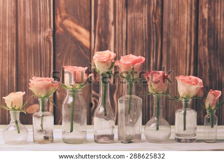 Pink roses in vintage bottles, home decor - stock photo