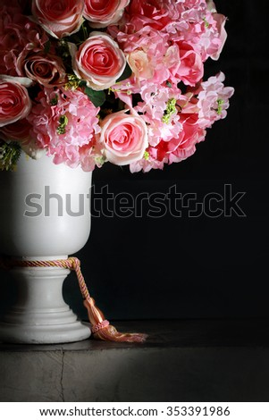 Pink roses in white roman vase,Vintage background.