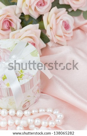 pink roses, round gift box and a pearl necklace on a silk fabric - stock photo