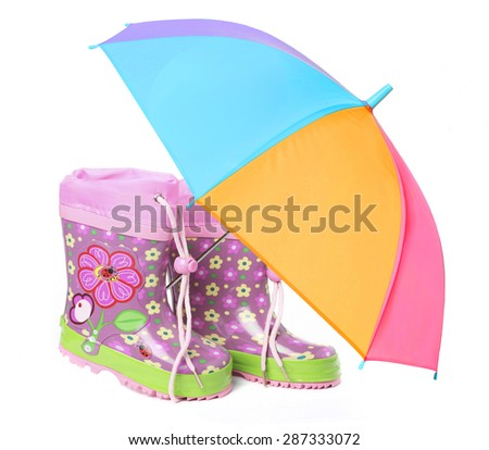 Pink rubber boots with floral print and a colorful umbrella isolated on a white background. Set for a child, for the girls for a comfortable walk in the rain. Symbol of protection, custody.