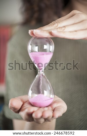 pink sand clock in woman hands over green background - stock photo