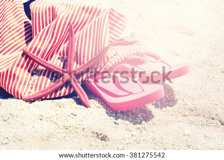 Pink Sea Clothes Flip Flops Bag Starfish on Sand Beach Summer Holiday Concept Copy Space Background for Design Toned - stock photo