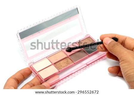 Pink set of pastel eyeshadows and hand isolated on white background - stock photo