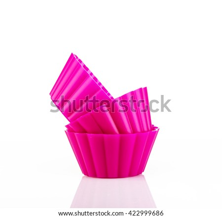 Pink silicone cupcake forms on white background - stock photo