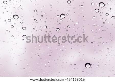 pink sky view through car window with rain drops, Driving in rain - stock photo