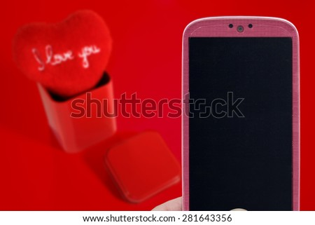 Pink smatrphone and I love you heart on red background. Idea for Valentines Day celebration, love, Father's or Mother's day, love apps, Internet, blogs and others. - stock photo