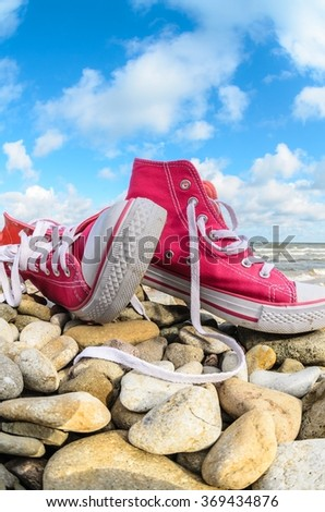 Pink sneakers on the stony beach