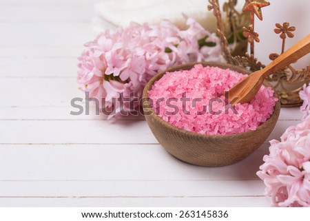 Pink spa  and wellness setting. Sea salt in wooden bowl,  flowers on white wooden background. Selective focus. Place for text.