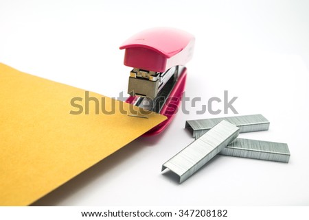 pink stapler on the white background