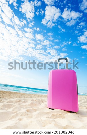 Pink suitcase bag on the sand on the beach with blue sky - stock photo