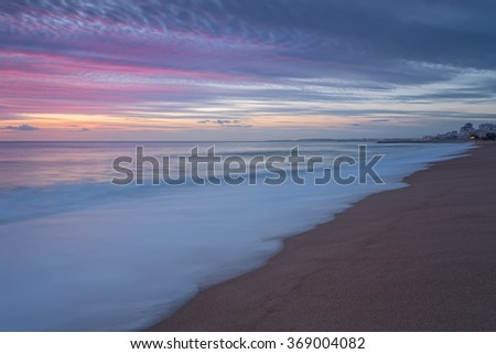 Pink sunset on the beach in Quarteira. Portugal for tourists. - stock photo