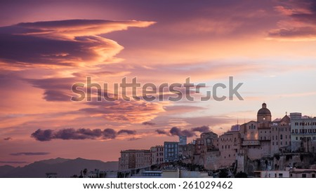 Pink sunset with clouds drawn by the wind in Cagliari - stock photo