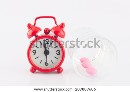 Pink tablet in dispensing glass and red alarm clock