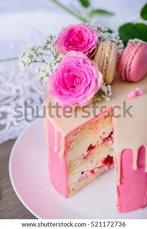 Pink three layered cake with roses and raspberry French macarons on top used for decoration
