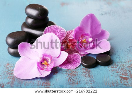 Pink tropical orchid flowers and spa stones on color wooden background