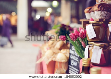 Pink tulips, baked goods, homemade preserves and jams on a farmer's market stand - stock photo
