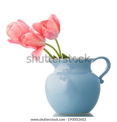 Pink tulips in a blue pitcher isolated on white. - stock photo