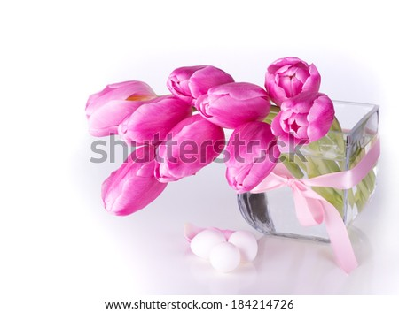 Pink tulips  in glass vase with eggs  . - stock photo