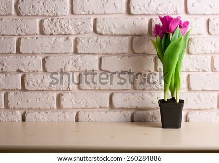 Pink tulips on wooden table over brick wall background - stock photo